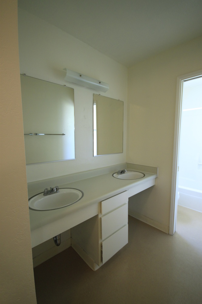 Vanity In Bathroom Has 2 Sinks, 2 Mirrors, And 3 Drawers. A Door Separates The Toilet And Tub Area