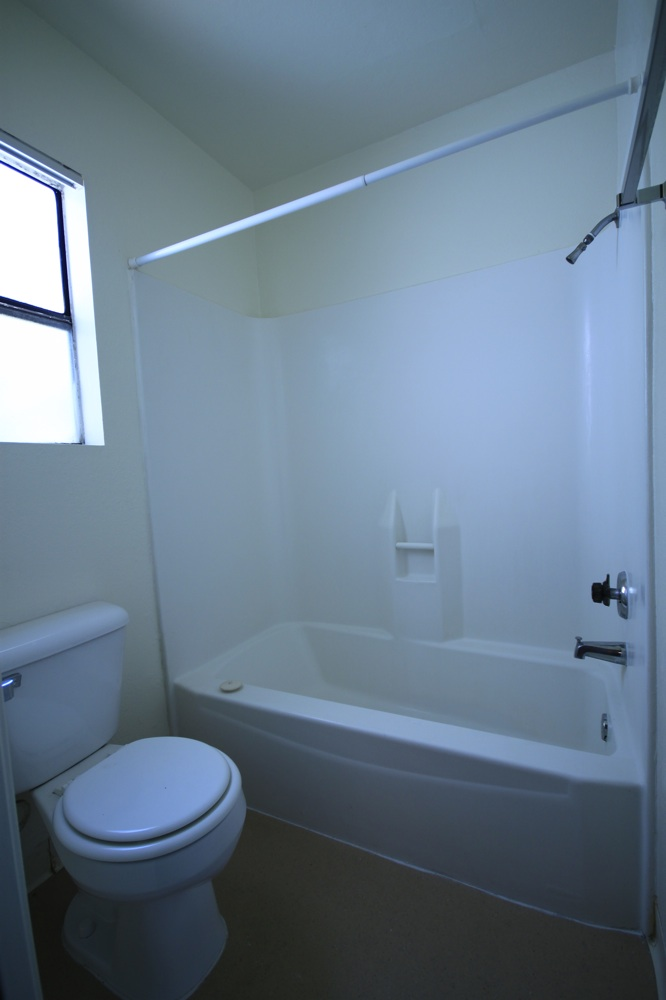 Bathroom Shows A Window Above The Toilet, A Shower And Tub With Shower Curtain Rod